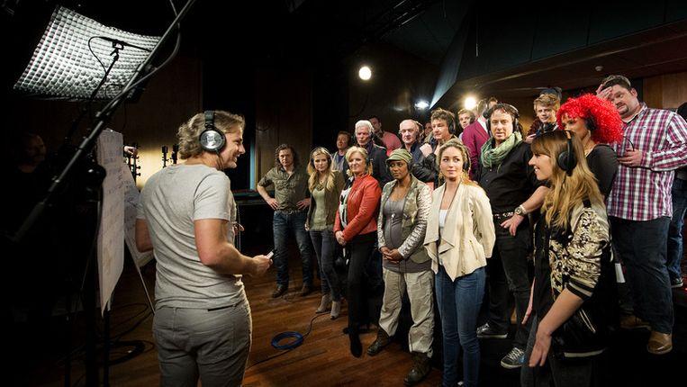Een groep BN'ers met op de voorgrond John Ewbank tijdens het opnemen van het Koningslied. Het lied zal op 30 april in Ahoy worden gezongen door een groot aantal nationale sterren. Beeld ANP Kippa