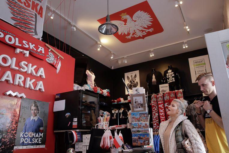 Klanten bekijken de koopwaar in de winkel Polska Marka in Lublin. Vooral de 'Westerplatte-lijn' loopt goed, met Poolse soldaten die standhielden tegen de nazi's.  Beeld Piotr Malecki