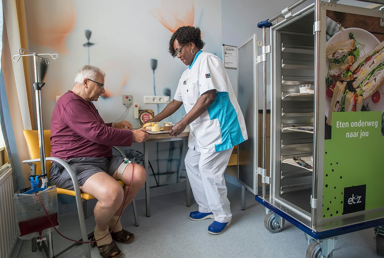 Toon Denissen verheugt zich op de lunch die zorgassistent Jarmine Donas hem brengt op de ziekenhuiskamer.