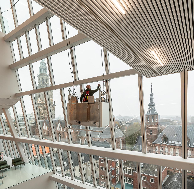 Het Groninger Forum 5 dagen voor de opening. De glazen gevel biedt telkens een ander perspectief. Beeld Harry Cock / de Volkskrant