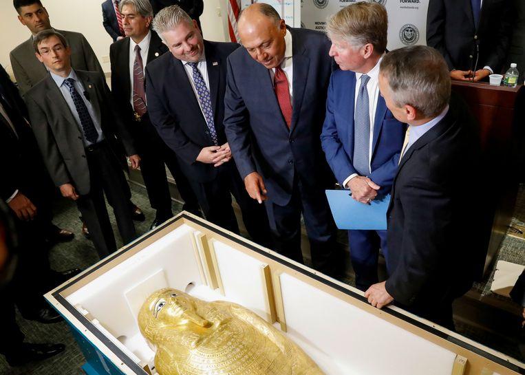 De Egyptische minister van buitenlandse zaken en de New Yorkse officier van justitie bestuderen de sarcofaag voor verzending.  Beeld REUTERS