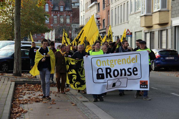 De groep trekt met vlaggen door de straten van Ronse.