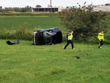 Auto met vader en dochter (9) vliegt van de weg en belandt op de kop in weiland in Pannerden
