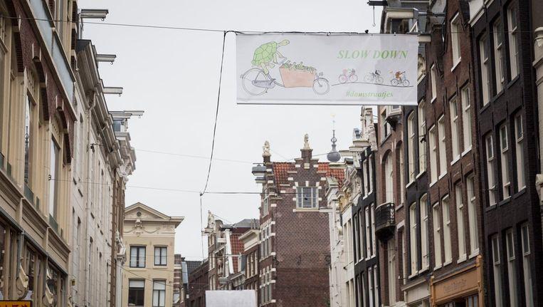 In de Damstraat hangt een spandoek met daarop de tekst 'slow down' Beeld Tammy Van Nerum