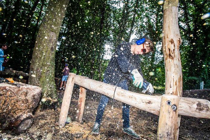 Deze jongen schuurt zelf een constructie waar hij mee bezig is op het schoolplein van De Boomhut in Arnhem. Vergroenen is het doel.