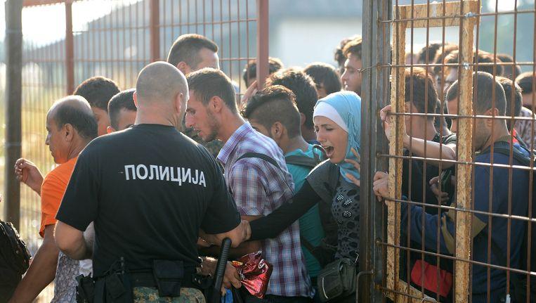 De grenspolitie in Macedonië laat een groep migranten en vluchtelingen het land in vanuit Griekenland. Beeld ap