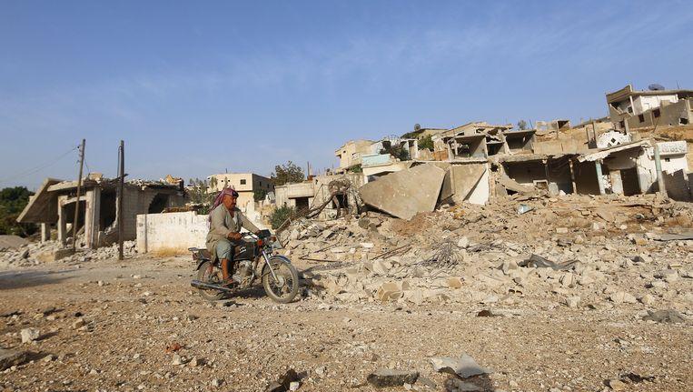 Een man rijdt langs een gebouw dat in puin ligt na een Russische luchtaanval op Latamneh, op het platteland van Hama. Beeld reuters