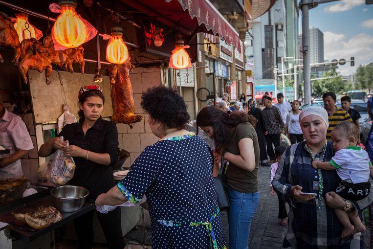 Een Oeigoerse vrouw verkoopt kip in het Oeigoerse deel van de hoofdstad Ürümqi.  Beeld Getty Images