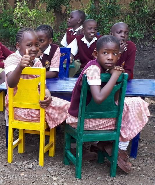 Kinderen van de Arya school zijn blij met de nieuwe stoelen en tafels.