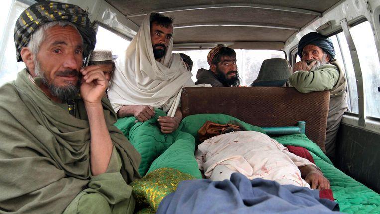 Afghaanse mannen met het lijk van een man die gisteren bij de schietpartij werd gedood. Beeld null