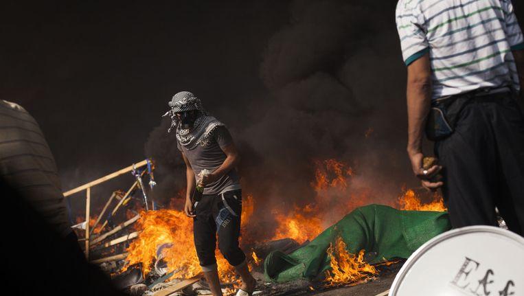 Een aanhanger van president Morsi passeert een vuurbarricade met een benzinebom in zijn hand. Beeld ap