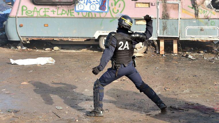 Een politieagent gooit een traangasgranaat. Beeld afp
