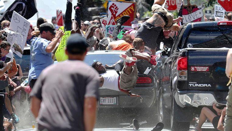 Mensen vliegen door de lucht als de auto zich door de groep tegendemonstranten boort. Beeld ap