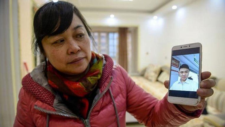 He Xiaoping (48) toont een foto van de jongen die ze 26 jaar geleden ontvoerde en opvoedde als was hij haar eigen kind.