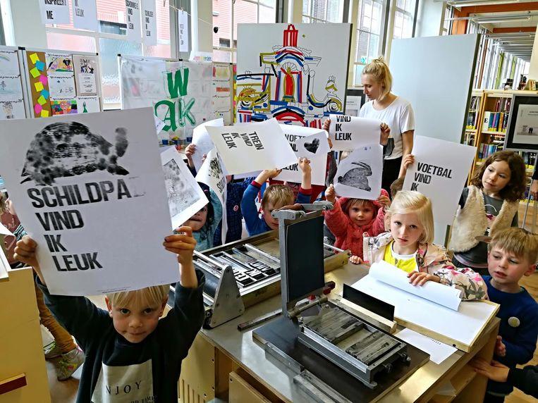 Kinderen tonen hun affiche bij de drukpers.