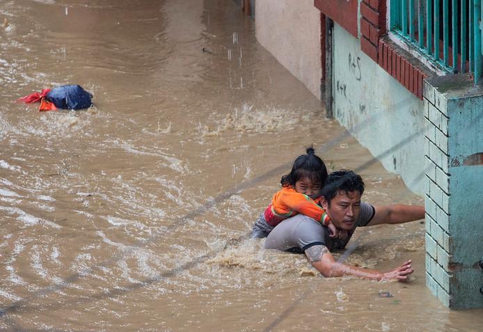 Un père sa fille à Katmandou alors que des pluies diluviennes s'abattent sur la ville