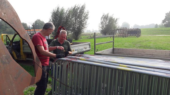Frank Kersten en Marcel Ruijter van BuitenWerk plaatsen de hekken die zondag gebruikt worden bij de start van de Niersdal Survivalrun Gennep.