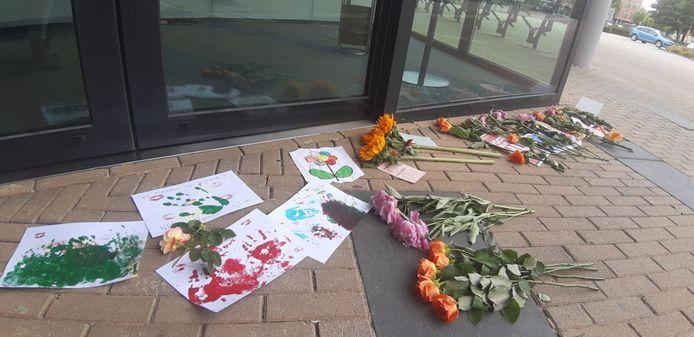 Bloemen en tekeningen gelegd op gemeentehuis in Zevenbergen.