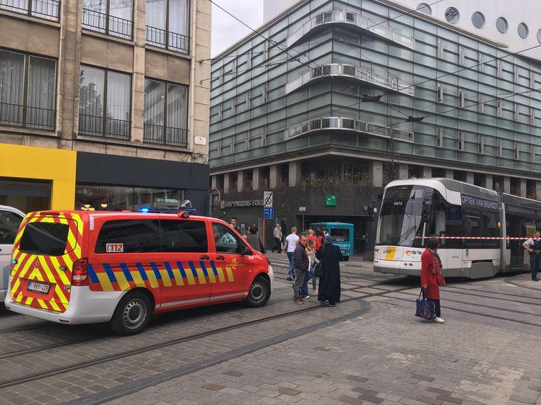 De man zit onder de tram gekneld met zijn been.