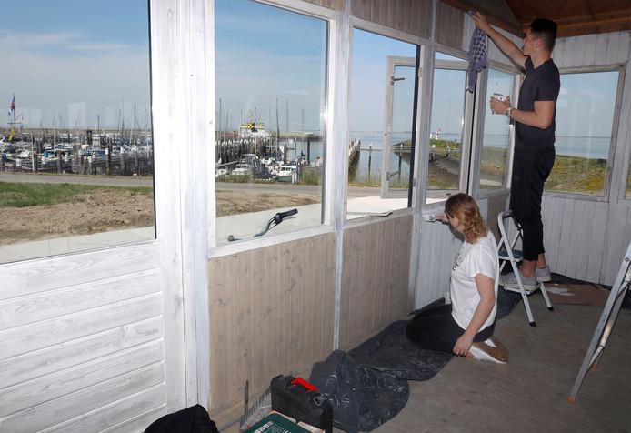 Jolie Herman (links) en Martijn Bakker bezig met het schilderen van het interieur van Foodjutters.