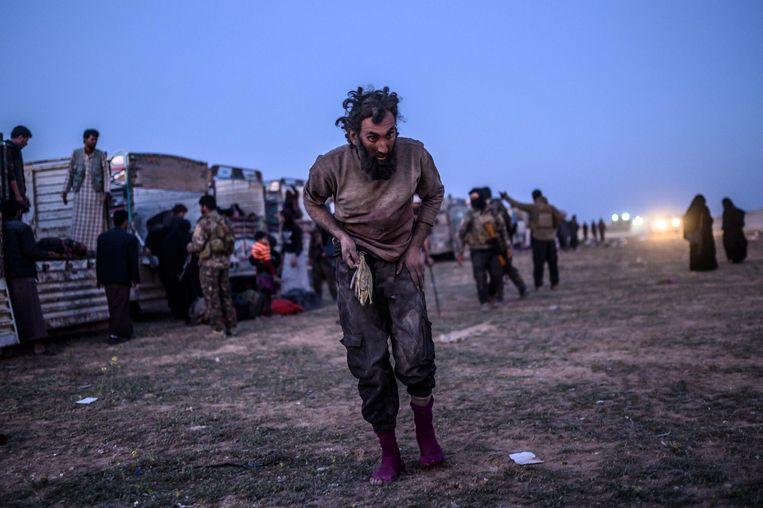 Een vermoedelijk lid van Islamitishe Staat wandelt voorbij leden van de SDF na het verlaten van Baghouz.