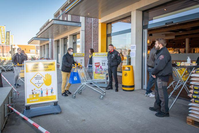 Ingehuurde beveiligers bij de ingang van een supermarkt houden een oogje in het zeil.