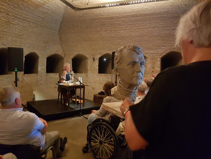 Tweemaal Adriaan van Dis: op de voorgrond in klei geboetseerd, door Carien van Dongen, op de achtergrond geeft 'het origineel' een lezing aan een volle zaal.