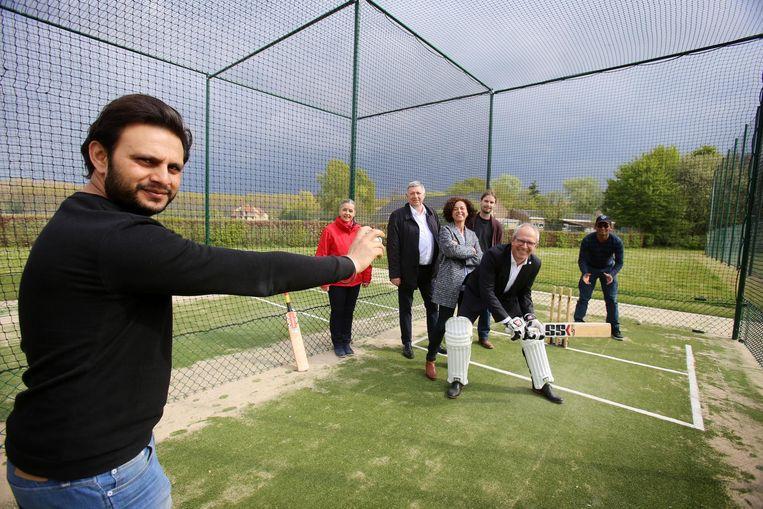 Voorzitter Singh Girjut gooit een balletje naar burgemeester Renaat Landuyt in de nieuwe oefenkooi voor cricket.