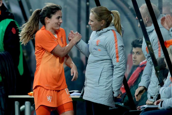 Daniëlle van de Donk (l) neemt na haar wissel de felicitaties van bondscoach Sarina Wiegman in ontvangst.
