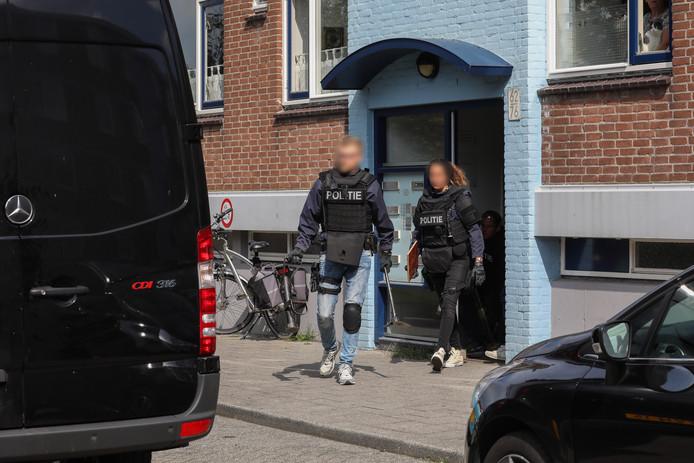 De politie doet inval in een woning aan de Mertensstraat, niet ver van de plek waar de Range Rover werd beschoten.