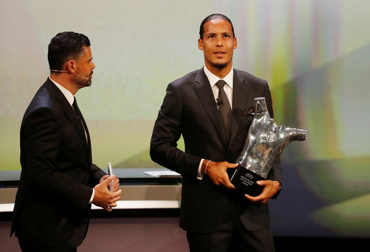 Virgil van Dijk neemt donderdagavond in Monaco de prijs voor Europees voetballer van het jaar in ontvangst. Naast hem de Amerikaanse presentator Pedro Pinto. Beeld REUTERS