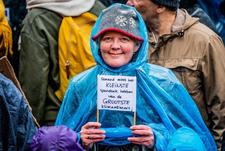 Een deelneemster aan de klimaatmars met een klein spandoek.  Beeld  Freek van den Bergh