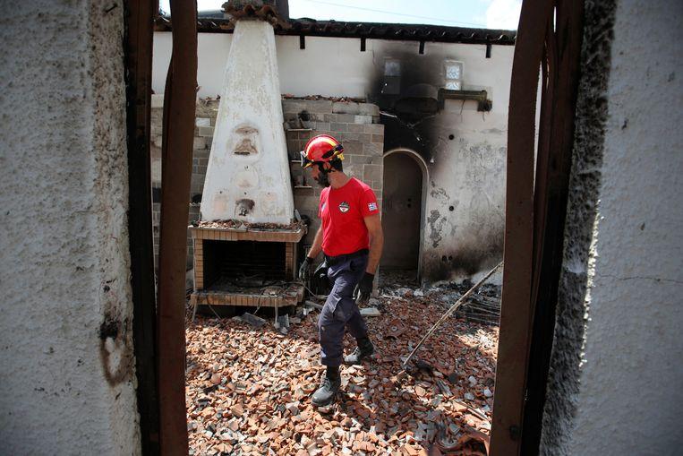 Een reddingswerker doorzoekt een afgebrand huis in Mati. Beeld AP