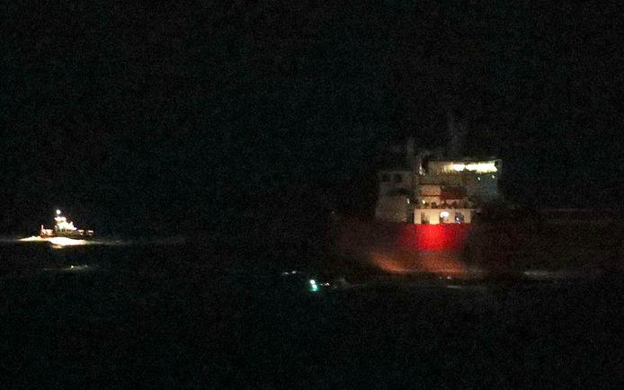 Een schip van de Britse kustwacht vaart na de actie weg bij de olietanker Nave Andromeda.
