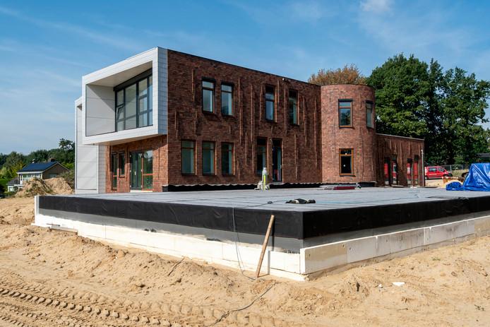 De achterkant van de school, met op de voorgrond het dak van de gymzaal. De grond wordt nog aangevuld, zodat het dak zo goed als geheel onder het maaiveld verdwijnt.