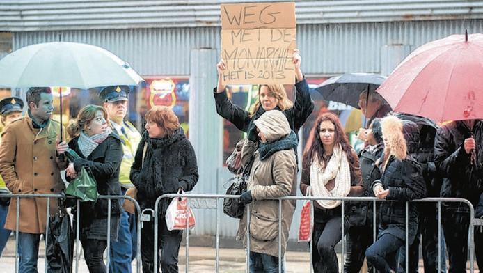 Joanna - ze wil niet met haar achternaam op de site- steekt voor het Beatrixgebouw haar protestbord omhoog. Links komen twee agenten aanlopen, die haar even later meenemen.