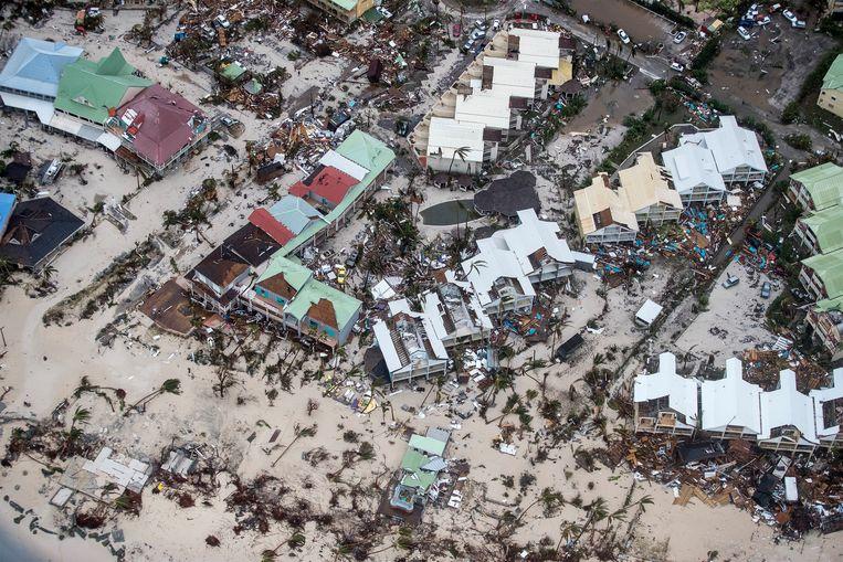 Afgeknapte palmbomen, afgerukte daken en omgewaaide gevels zijn te zien op deze luchtfoto van Sint Maarten, gemaakt vanuit een Nederlandse marine-helikopter. Beeld AP