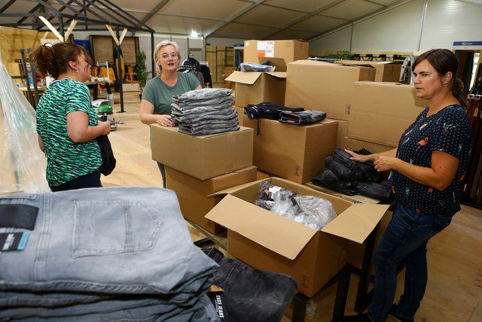Dozen vol met nieuwe bestellingen worden uitgepakt in de tijdelijke kledingzaak.