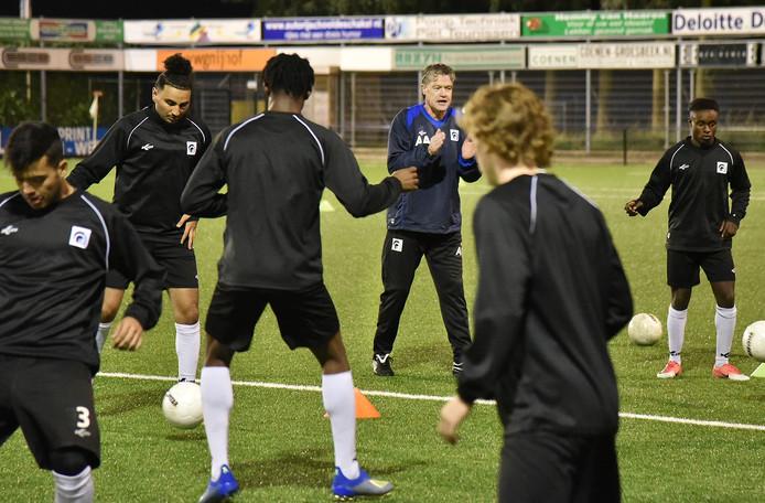 Arno Arts (met lange broek) coacht zijn spelers op de training van Achilles'29.