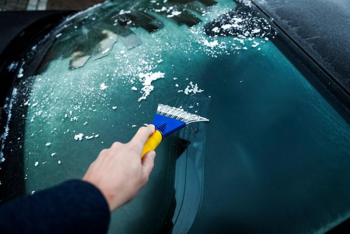 Een man krabt de voorruit van zijn auto schoon.