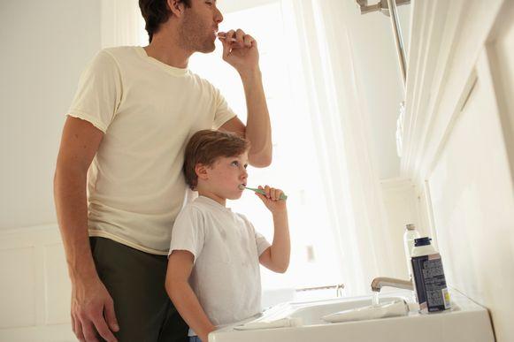 Een vader en zoon poetsen hun tanden samen in de badkamer.