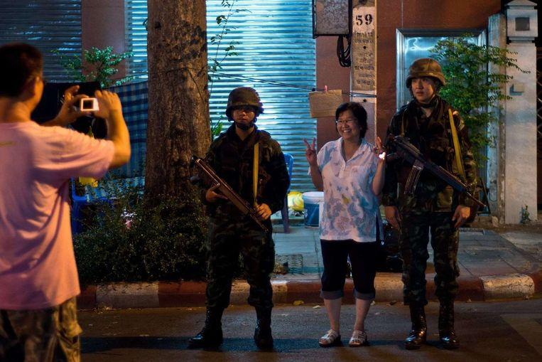 Een Thaise anti-regeringsdemonstrant gaat op de foto met Thaise militairen in Bangkok. Beeld afp