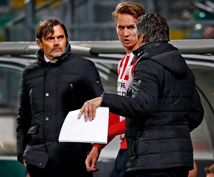 Ruud Brood, assistent-coach van PSV, geeft spits Luuk de Jong aanwijzingen. Links trainer Phillip Cocu.