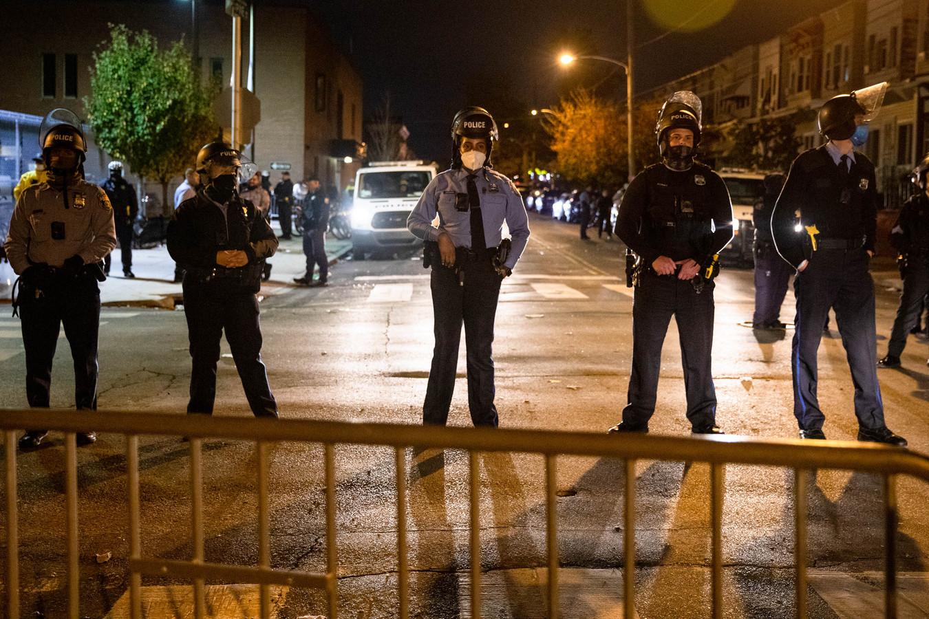 Politieagenten bewaken een politiebureau in Philadelphia tijdens de avondklok die donderdag gold in de stad.