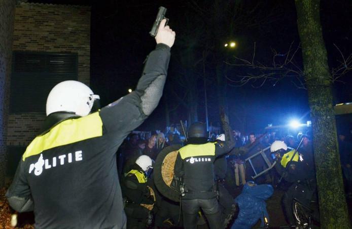 Een agent lost een waarschuwingsschot tijdens de rellen in Geldermalsen. Foto: