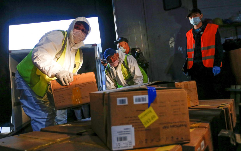 Douaniers in Kazachstan laden coronahulppakketten uit, geschonken door AliBaba-oprichter Jack Ma. Beeld Pavel Mikheyev / Reuters