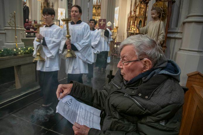 Pastoor Jan van Noorwegen neemt in de zijbeuk een pamflet als protest tegen de voorgenomen sluiting van zijn Heuvelse kerk door.