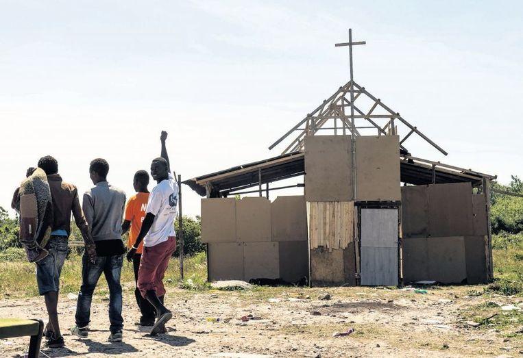 In het provisorische vluchtelingenkamp bij Calais hebben bewoners eigenhandig een kerk gebouwd. Daar kunnen ze een schiet- of ander gebedje doen voor ze een poging wagen om het Kanaal over te steken. Beeld afp