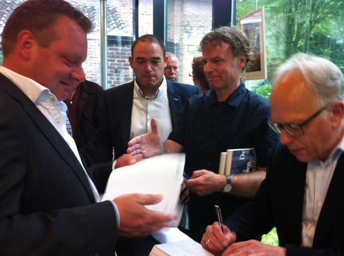 Gerard Buenen en Winy Maas hebben het druk met signeren van het boek over de Glazen Boerderij.
