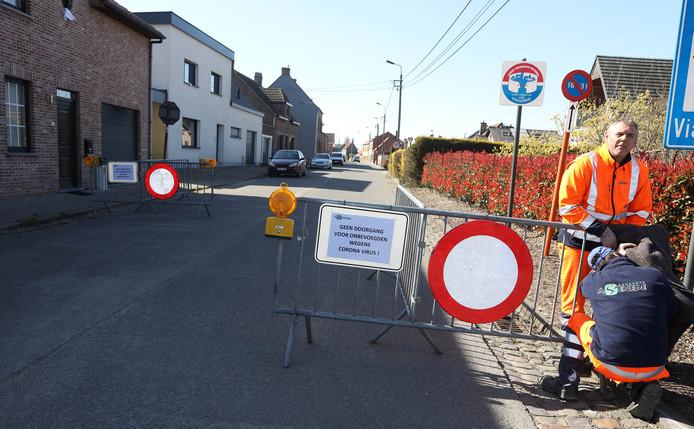 Wegafzetting bij 't Staak op de grens bij Sas van Gent met het Belgische Assenede, gemeentewerkers van Assenede voeren nog wat laatste werkzaamheden uit.